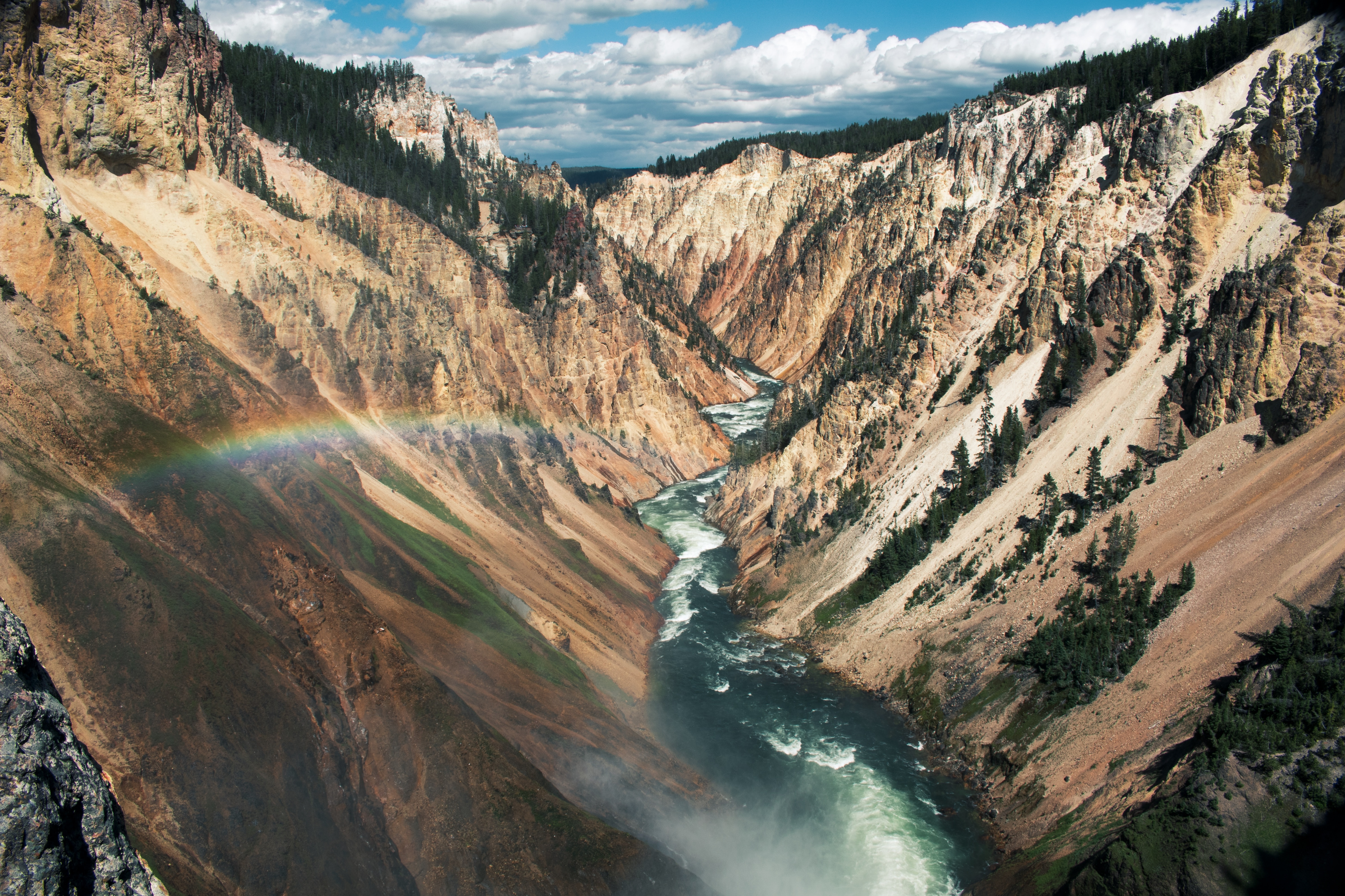 A river in a mountain gorge with a rainbow