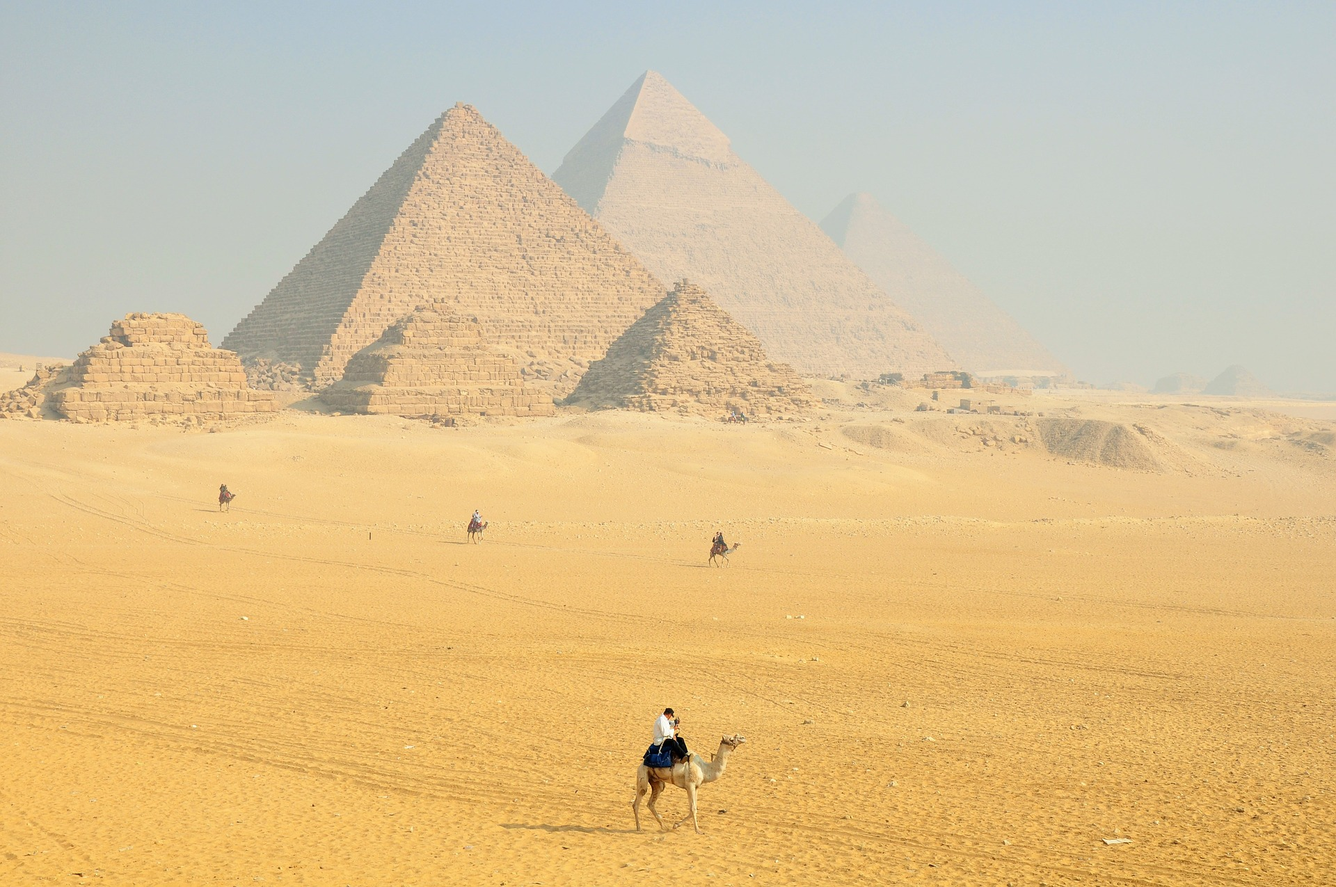 Camel riders in front of the pyramids in Egypt